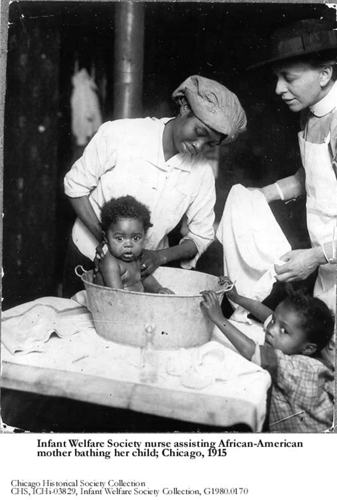 historical photo of a white nurse assisting an African-American woman bathing her baby
